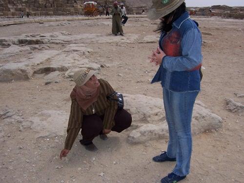 Rhoda, arqueóloga, foi um de meus guias no Egito. Observem a roupa fechada, a cabeça coberta por lenço. (Aqui, ela desenha na areia, ao lado da Pirâmide de Queóps, um esquema explicativo para a minha linda irmã — com quem aprendi a ser explorador durante viagens.)