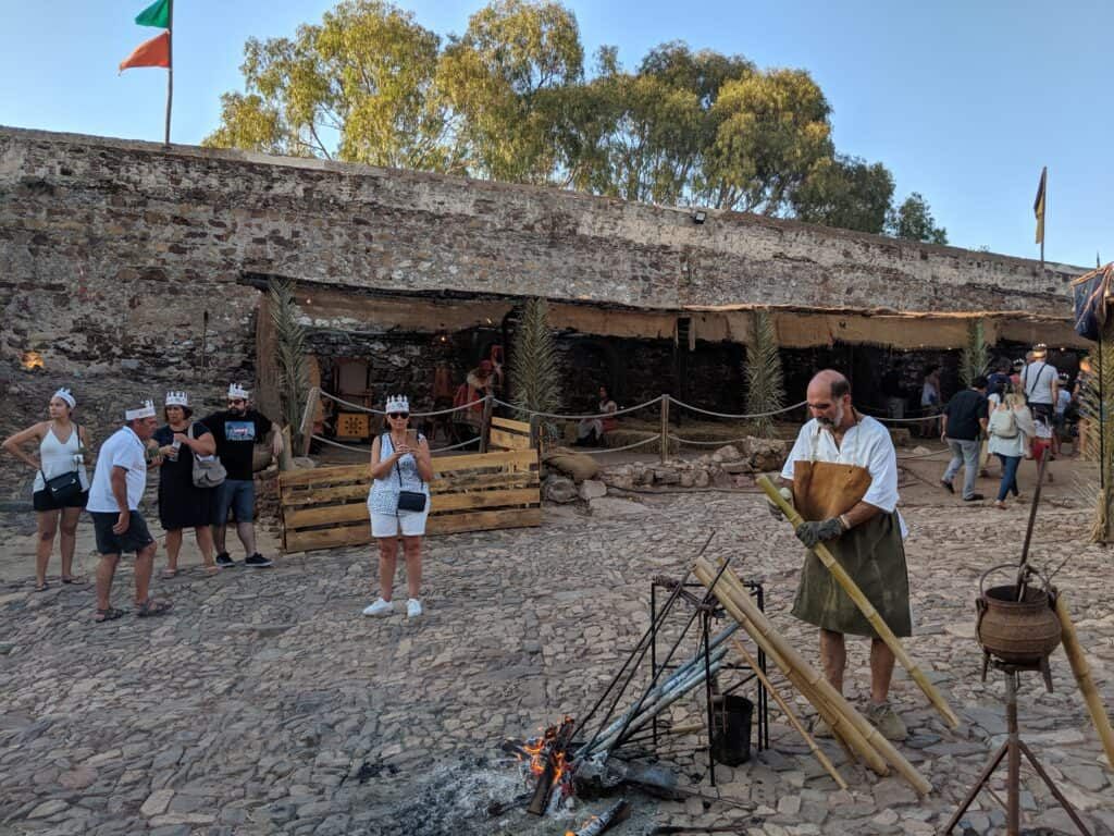 Homem faz fogueira dentro do castelo, durante uma feira medieval em Portugal.
