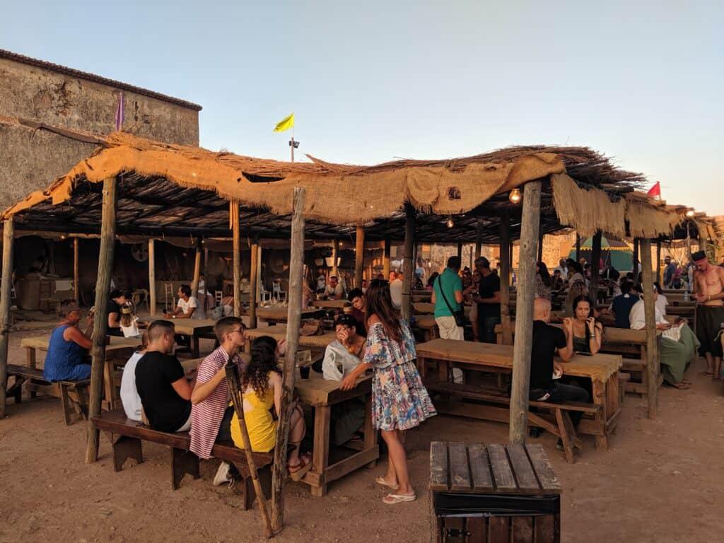 Visitantes da Feira Medieval em Portugal em barraca de comidas e bebidas