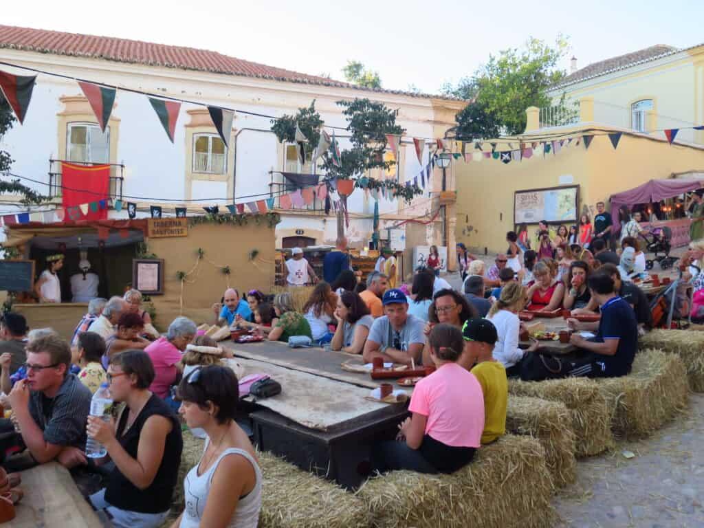 Pessoas sentadas em bancos de palha para comer e beber