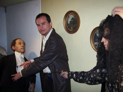 Bonecos das histórias: a assassina, com Glauco no meio mostrando o ferimento a bala