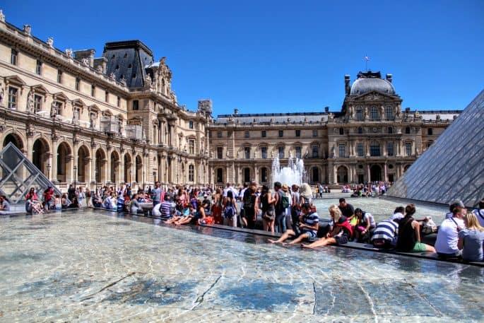 Na área externa do Museu do Louvre, turistas, no verão, tentam refrescar-se nas fontes