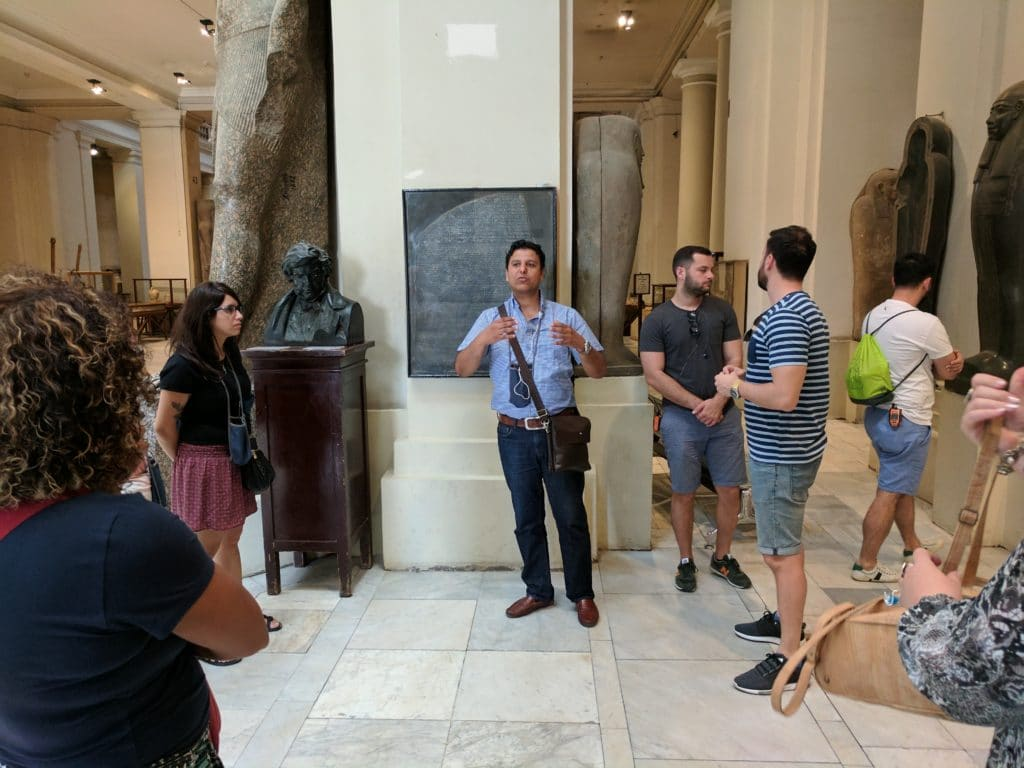 A tour guide explains an item in the museum