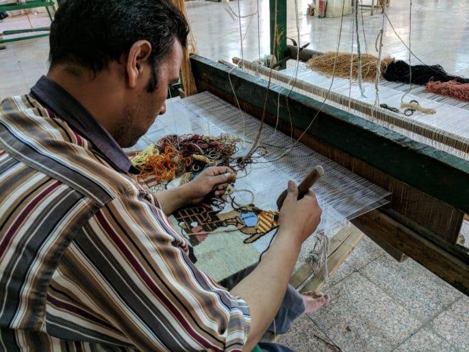 Interior da fábrica de tapetes no Egito. Um artista trabalha.