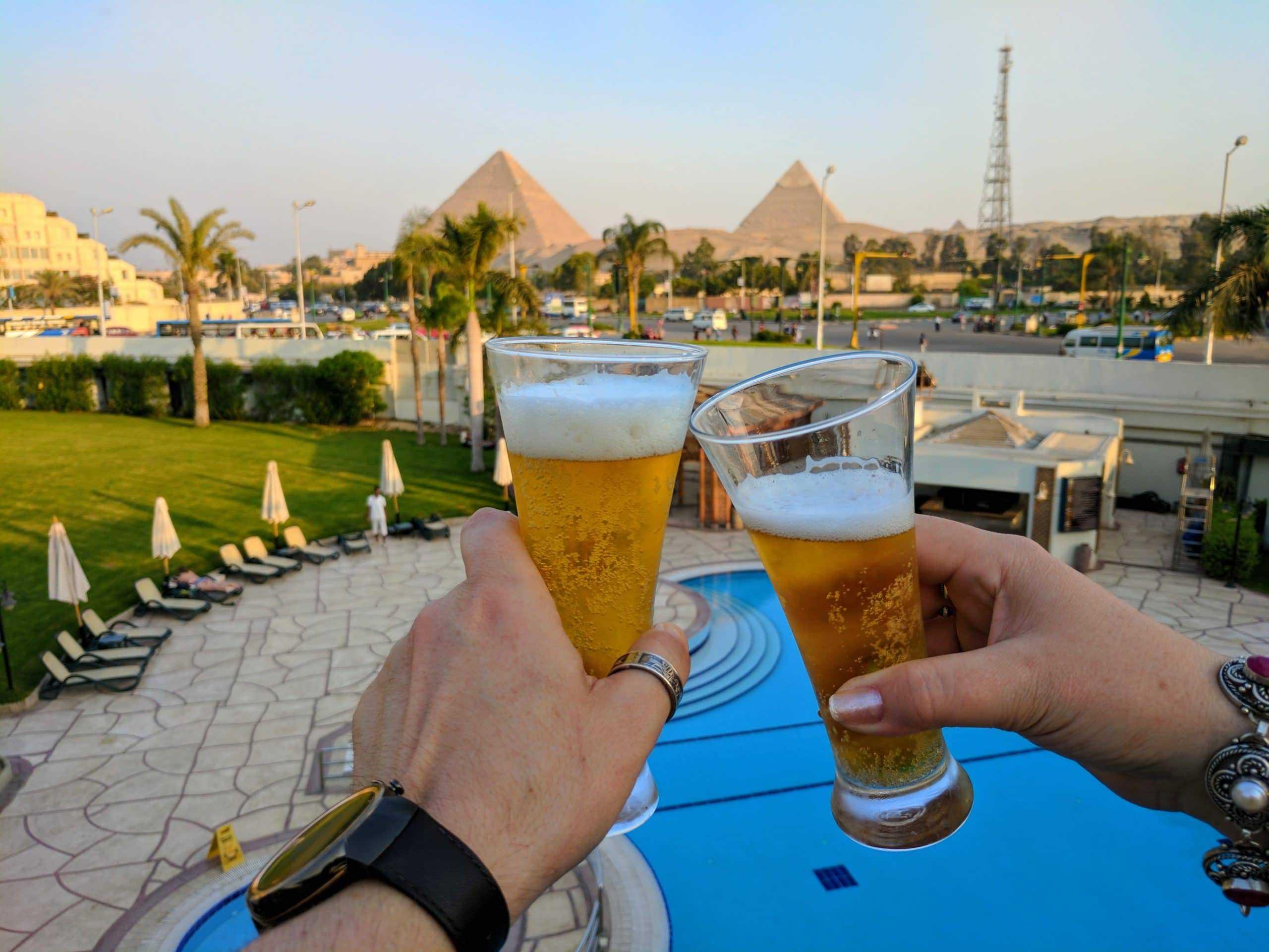 Um brinde de cerveja com as Grandes Pirâmides no fundo.