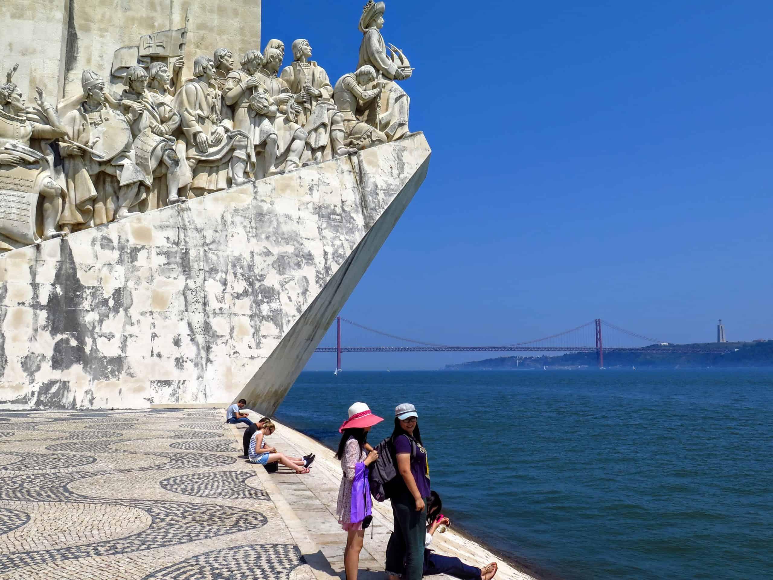 O monumento, o Rio Tejo e a Ponte 25 de Abril.